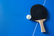 Leinwandbild Motiv A racket for table tennis with a ball lying on the blue table. A view from above.