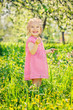 Leinwandbild Motiv Happy little girl playing in sunny spring garden
