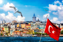 Landscape Of Istanbul - City Skyline Of The Old Town Near Galata Bridge And A Quayside Of Beyoglu District. Seaside View With Passenger Ships, Turkish Flag And Flying Birds Over The Golden Horn.