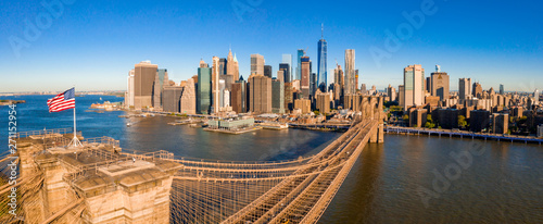American flag on top of the Brooklyn bridge with Manhattan view on the background.