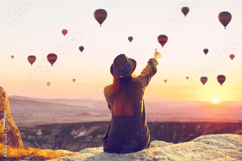 Obraz na plátne A woman alone unplugged sits on top of a mountain and admires the flight of hot air balloons in Cappadocia in Turkey