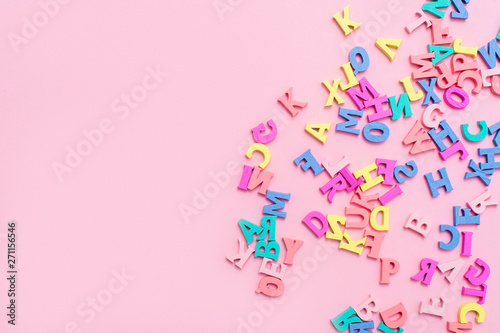 Valokuva  Many multicolored wooden letters on a pink background