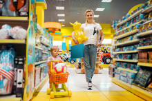 Mother With Girl Buying A Lot Of Toys In Store