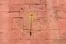 Golden Sundial On Sandstone Facade