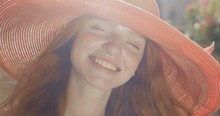 Portrait Of A Young Beautiful Red-haired Girl In A Wide Red Hat. The Girl Looks Very Happy And Fun On A Sunny Day. In Slow Motion. Shot On Canon 1DX Mark2 4K Camera