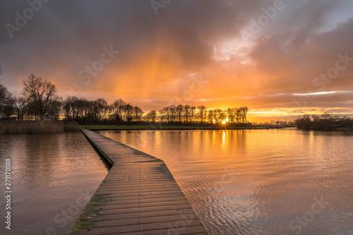 Poster Cappuccino Wooden walkway in lake under orange sunset