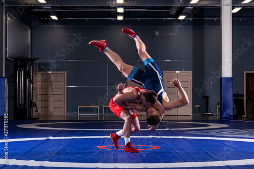 Obraz Two strong wrestlers in blue and red wrestling tights are wrestlng and making a  making a hip throw  on a yellow wrestling carpet in the gym. Young man doing grapple. - fototapety do salonu