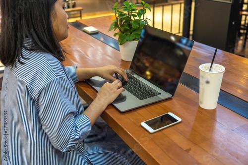 Fototapeta Young woman freelance working on laptop and mobile phone obraz na płótnie