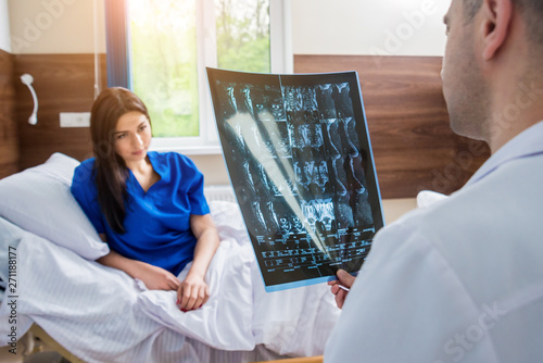Traumatologist showing MRI film to patient in hospital.