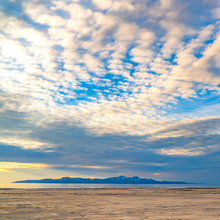 Square Boundless Blue Sky With Gray And White Clouds Over A Vast Sandy Shore