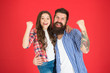Leinwanddruck Bild - Successful team. Man bearded father and cute little girl daughter on red background. Celebrate fathers day. Family values concept. Family bonds. Friendly relations. Father hipster and his daughter