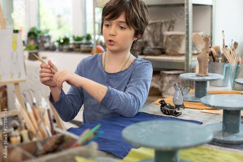 Poster Ecole de Danse Boy taking little brush while sculpting clay figures