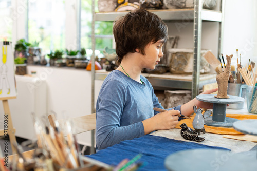 Photo sur Toile Les Textures Dark-haired talented boy sculpting figures with clay