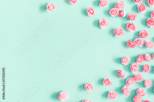 Flowers composition. Pink rose flowers on mint background. Flat lay, top view, copy space