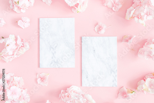 Flowers composition. Hydrangea flowers,paper blank on pastel pink background. Flat lay, top view, copy space