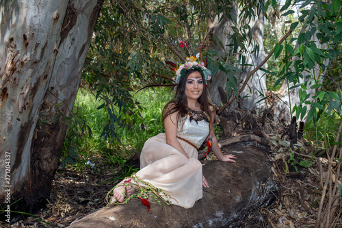 Cuadros en Lienzo Girl in the dress Pocahontas sitting on a tree trunk on the background of green