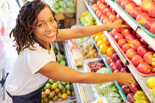 Fotomural Pretty smiling Black woman working at fruit department at grocery store