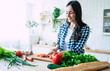Leinwandbild Motiv Beautiful young woman is preparing vegetable salad in the kitchen. Healthy Food. Vegan Salad. Diet. Dieting Concept. Healthy Lifestyle. Cooking At Home. Prepare Food. Cutting ingredients on table