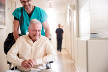 Male Orderly Pushing Senior Male Patient Being Discharged From Hospital In Wheelchair