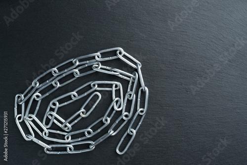 Vászonkép Convoluted shiny metal chain on a dark stone slate plate.