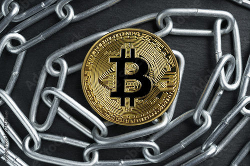 Valokuva  Physical Bitcoin gold coin on a convoluted shiny metal chain.