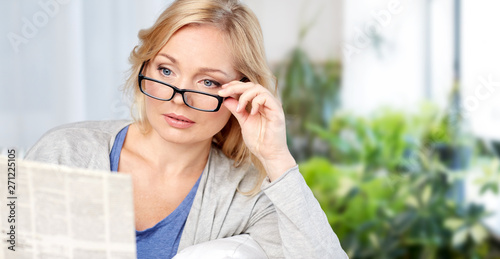 obraz lub plakat news, press, mass media and people concept - woman in eyeglasses reading newspaper at home