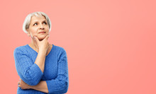 Old People And Decision Making Concept - Portrait Of Senior Woman In Blue Sweater Thinking Over Pink Or Living Coral Background