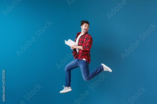 Jumping young man with book on color background Canvas Print