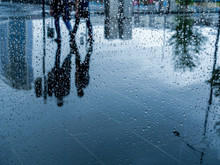 Rain Drops On Glass With Blurred Reflection On Wet Ground Of People Walking On Urban Street.