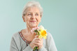 canvas print picture - Portrait of senior woman with bouquet of flowers on grey background