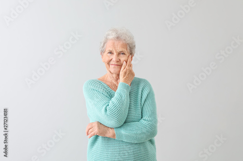 Portrait of senior woman on light background