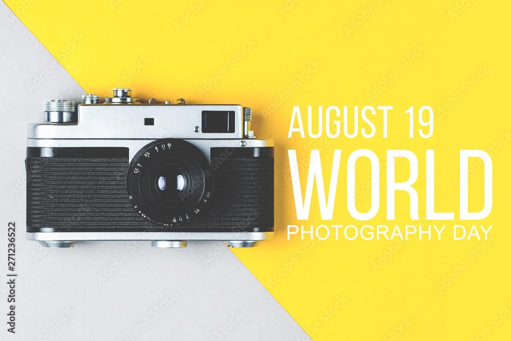 Fototapety, obrazy: Old retro photo camera on grey-yellow background. World photography day poster