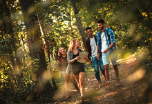Group Of Four Friends Having Fun Hiking Through Forest Together.