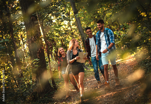 Group of four friends having fun hiking through forest together. Fototapeta
