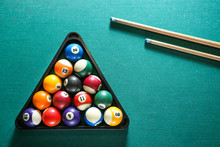 Billiard Balls In Triangle Rack With Cues On Table