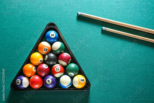 Canvas Print Billiard balls in triangle rack with cues on table