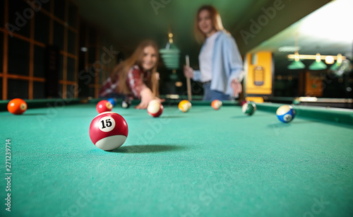 Fotografie, Obraz Young women playing billiard in club