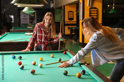 Photo Young women playing billiard in club