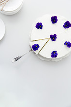 A Cut Piece From A White No Bake Cheesecake With Edible Purple Pansy Flowers.