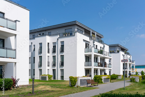 Fototapeta modern real estate and condominium with several apartments and penthouses white and gray facade surrounded by clean grassy areas obraz