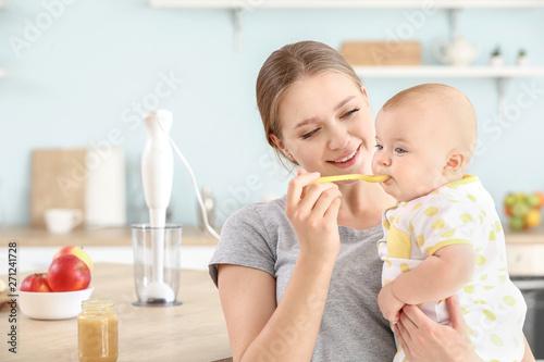 Mother feeding her little baby in kitchen at home Fototapeta