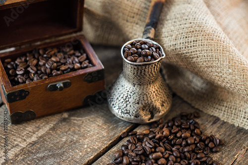 Staande foto Koffiebonen coffee beans and turk on a wooden background