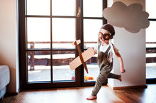 A Toddler Boy With Carton Plane Playing Indoors At Home, Flying Concept.