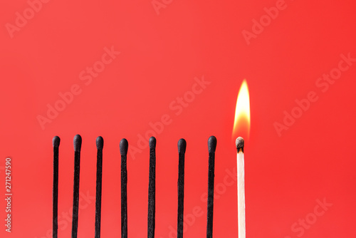 Fotomural  One burning match among burnt-out ones on color background