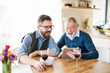 canvas print picture Adult hipster son and senior father sitting at the table indoors at home.