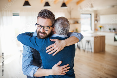 Fotografie, Obraz  An adult son and senior father indoors at home, hugging.