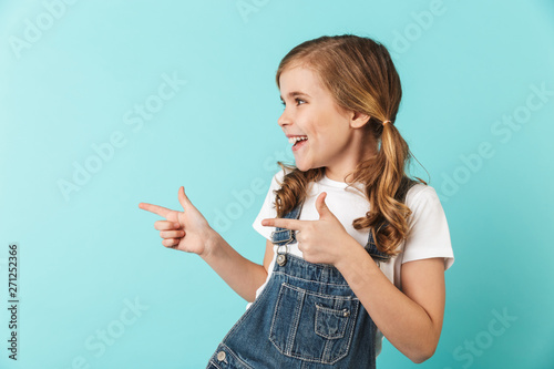 Pretty young little girl posing isolated over blue wall background pointing.
