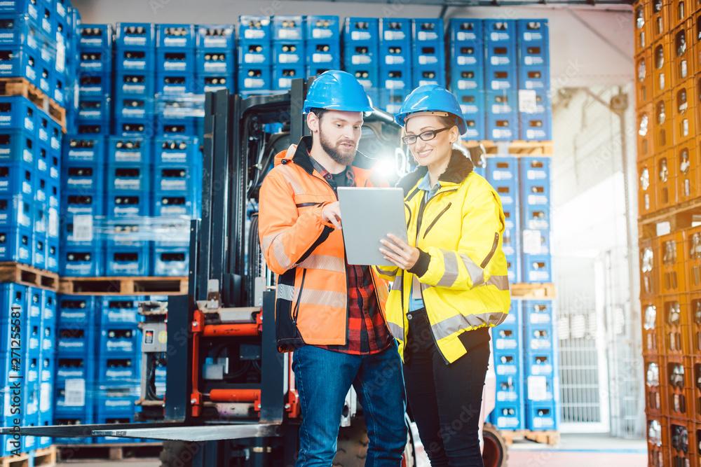 Valokuva Mann und Frau als Arbeiter im Logistikzentrum nutzen Computer