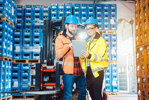 Mann und Frau als Arbeiter im Logistikzentrum nutzen Computer Canvas-taulu