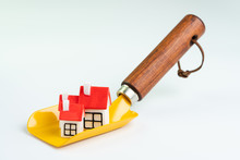 Building The House, Architecture Construction Or Mortgage Loan Concept, Small Cute Miniature Houses With Red Roof On Yellow Post Hole Digger Shovel On White Background